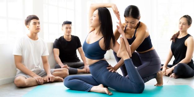 Persone asiatiche panoramiche che imparano lezione di yoga in palestra. istruttore coaching e regolare la posa corretta