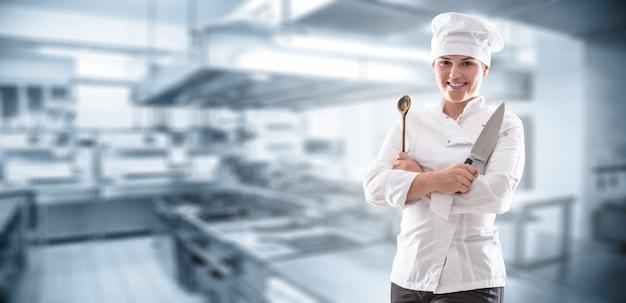 Banner panoramico di uno chef con le mani incrociate in possesso di un coltello e un cucchiaio di legno e in piedi davanti alla cucina del ristorante.