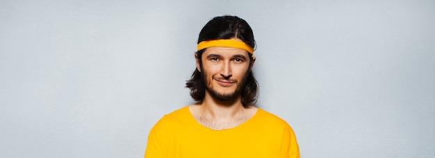 Banner panoramico ritratto di giovane uomo sicuro di sé in giallo con capelli lunghi su sfondo grigio strutturato.