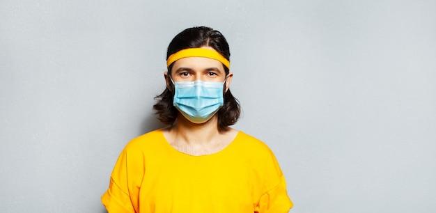 Banner panoramico ritratto di giovane ragazzo con maschera medica sul viso contro i virus che indossa camicia gialla e fascia sulla testa. fondo della parete strutturata grigia.