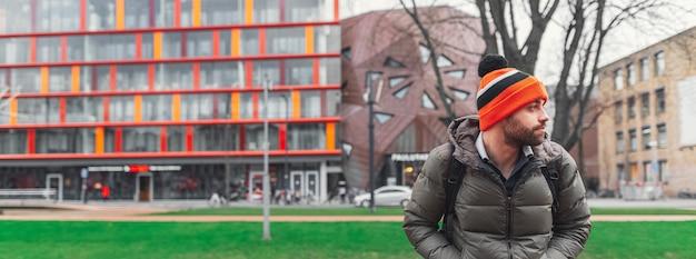 Banner panoramico ritratto di giovane ragazzo con cappello arancione sulla superficie della città moderna di primavera.