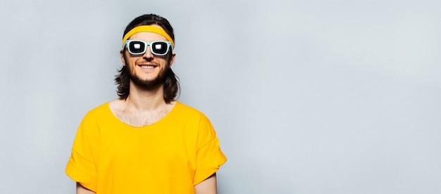 Banner panoramico ritratto di giovane uomo felice in giallo con occhiali da sole su sfondo grigio strutturato con spazio copia.