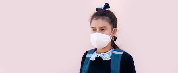 Banner panoramico della ragazza della scuola che indossa una maschera medica, su sfondo rosa.