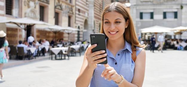 Banner panoramico di donna attraente sorridente che prenota online con smartphone in piazza della città