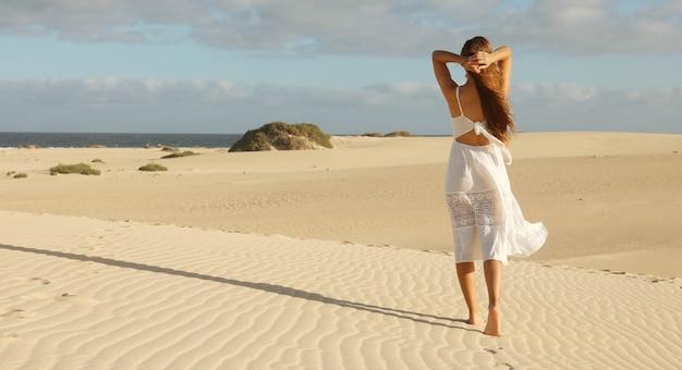 Vista panoramica della bandiera di bella donna con vestito bianco che cammina sulle dune del deserto al tramonto. ragazza che cammina sulla sabbia dorata su corralejo dunas, fuerteventura.