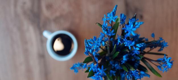 Primo piano panoramico di vista dell'insegna dei fiori delle viole su fondo vago della tavola di legno e della tazza di ceramica con caffè.