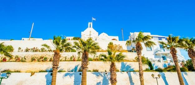 Vista panoramica dal basso dell'antica chiesa greca con bandiera sollevata su di essa e alte palme di fronte ad essa sulla strada greca