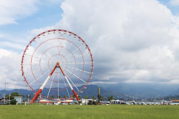 Ruota panoramica panoramica nel parco delle meraviglie sull'argine della città di batumi contro un cielo nuvoloso. georgia
