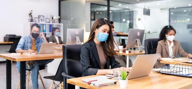 Il gruppo panoramico del team di lavoratori aziendali indossa una maschera protettiva nel nuovo ufficio normale con pratica a distanza sociale con gel alcol disinfettante per le mani sul tavolo per prevenire la diffusione del coronavirus covid-19