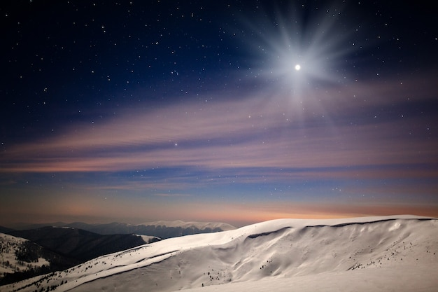 Vista panoramica notturna della valle di montagna invernale ricoperta di neve, montagne e luna sopra nella notte invernale con molte stelle nel cielo