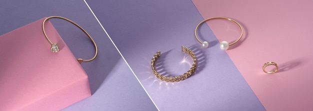 Collage fotografico panoramico di gioielli d'oro su sfondo rosa e viola