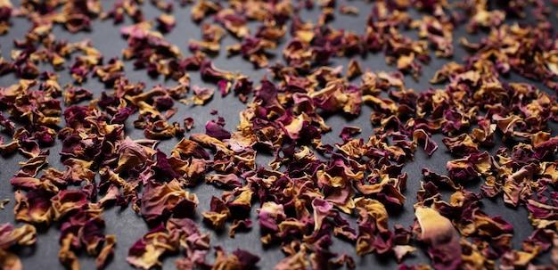 Foto panoramica di foglie essiccate di rosa tea, sul tavolo nero. idea del modello.