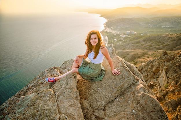 Foto panoramica di una donna felice che ha conquistato la cima di una scogliera con una bellissima vista sul mare