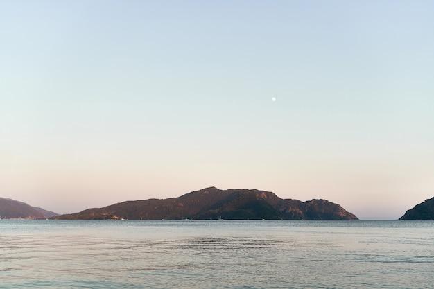 Foto panoramica del mare e delle colline al tramonto. in viaggio verso la natura
