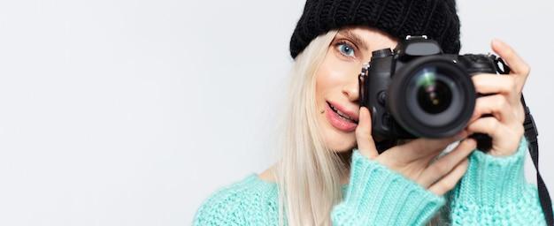 Ritratto panoramico della ragazza bionda che prende foto sulla macchina fotografica di dslr, su bianco.
