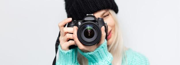 Ritratto panoramico di bella ragazza che prende foto sulla fotocamera dslr, su bianco. Foto Premium