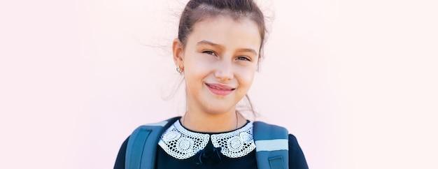 Ritratto panoramico di un'adolescente sorridente su sfondo rosa pastello.