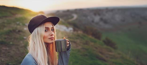 Ritratto panoramico di giovane ragazza bionda che tiene tazza d'acciaio sulla cima delle colline al tramonto.