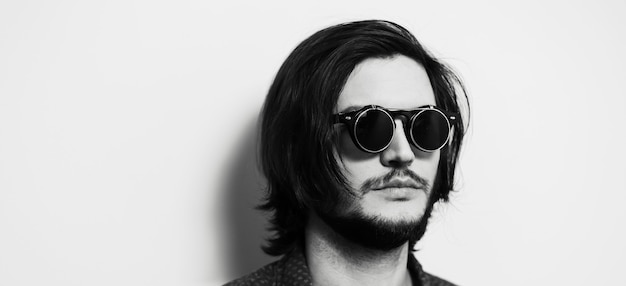 Ritratto panoramico di giovane con capelli lunghi e occhiali scuri.