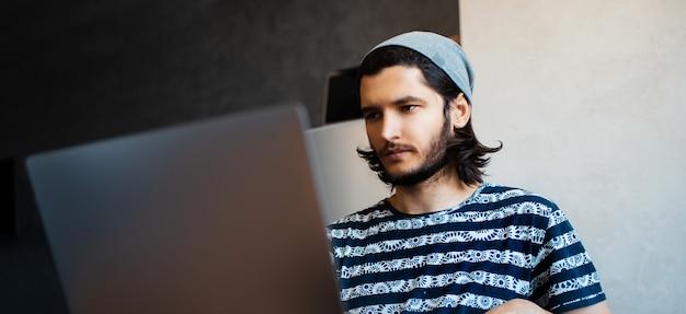Ritratto panoramico del giovane che lavora a casa al computer portatile.