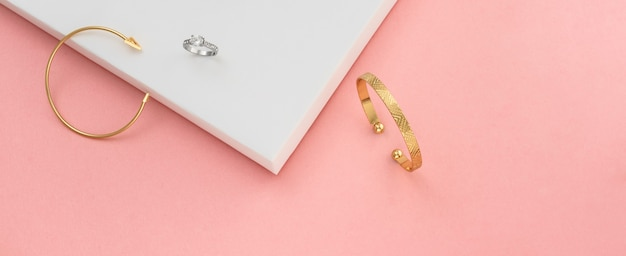 Colpo panoramico di bracciali e anello su sfondo rosa e bianco con spazio di copia