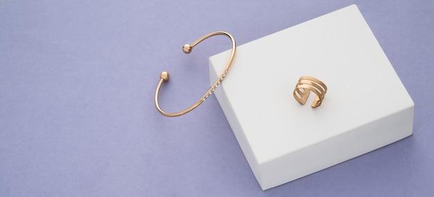 Scatto panoramico di bracciale e anello d'oro su scatola bianca su sfondo viola
