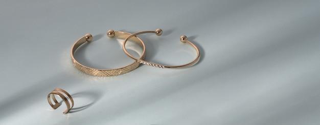 Scatto panoramico di braccialetti d'oro e anello d'oro su sfondo blu con spazio di copia