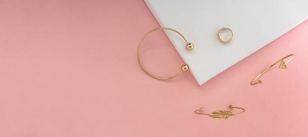 Colpo panoramico di gioielli d'oro su sfondo rosa e bianco con spazio di copia