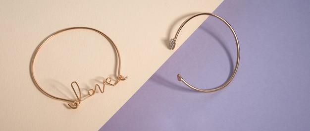 Scatto panoramico del braccialetto a forma di parola d'amore su sfondo di colori pastello con spazio di copia