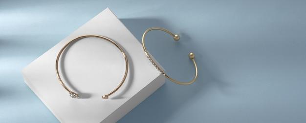 Scatto panoramico di braccialetti moderni su scatola bianca su sfondo blu con spazio di copia