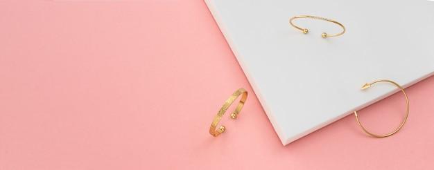 Colpo panoramico di tre moderni braccialetti d'oro su sfondo bianco e rosa con spazio di copia