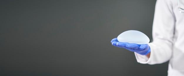 Panoramica di una protesi mammaria al silicone nelle mani di un medico