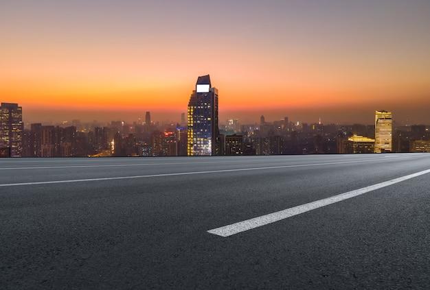 Orizzonte panoramico e strada asfaltata vuota con edifici moderni