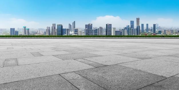 Orizzonte panoramico e piastrelle quadrate vuote con edifici moderni