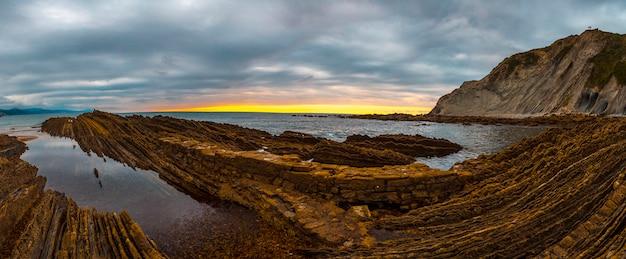 Panoramica di un tramonto sulla spiaggia di itzurun nel flysch di zumaia. paese basco