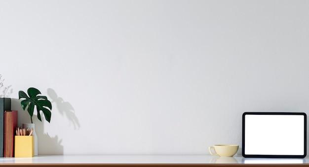 Vista panoramica del tablet schermo vuoto e oggetto decorativo su tavolo bianco con spazio copia.