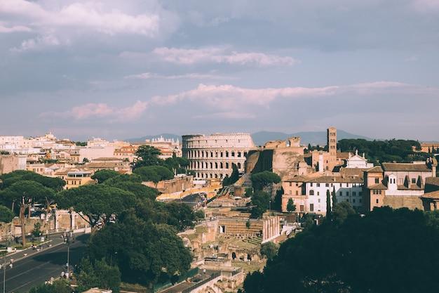 Vista panoramica della città di roma con il foro romano e il colosseo dal monumento a vittorio emanuele ii noto anche come il vittoriano. giornata di sole estivo e cielo blu drammatico