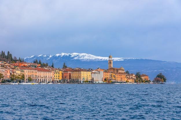 Vista panoramica della città salò e l'argine sul lago di garda sullo sfondo sono le alpi innevate. periodo invernale. lombardia, italia