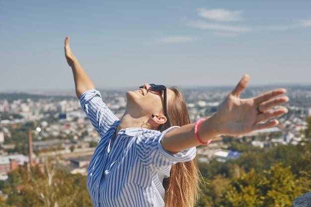 Vista panoramica di una città e una giovane donna in occhiali da sole in primo piano alzando le braccia e guardando il cielo