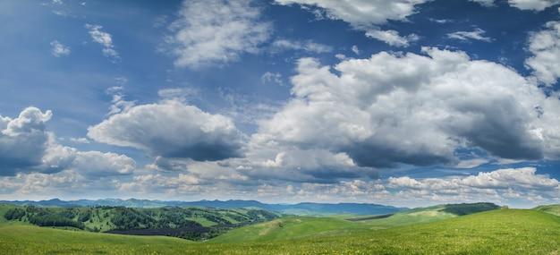 Vista panoramica di verdi colline e pittoresco cielo azzurro con nuvole bianche
