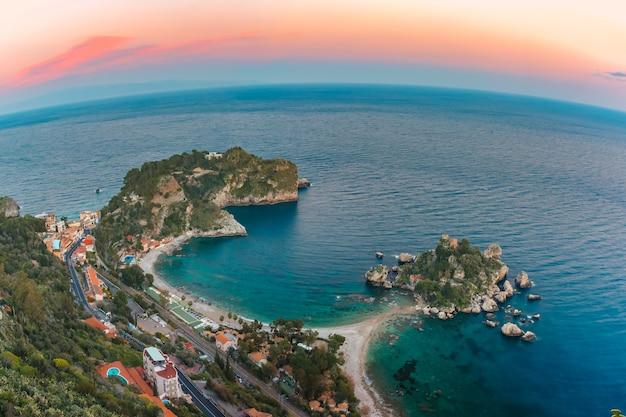 Vista panoramica della baia di isola bella, la perla del mar ionio, al tramonto, taormina, sicilia