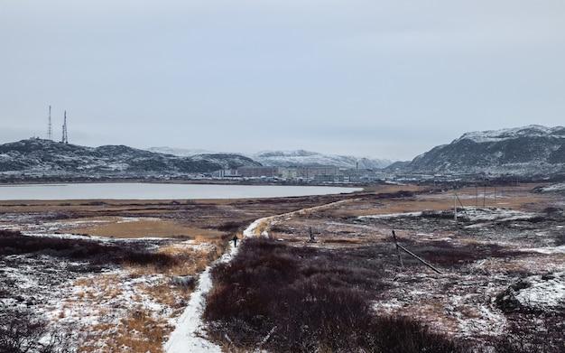 Vista panoramica uno stretto sentiero che porta in lontananza al villaggio artico situato tra le colline polari