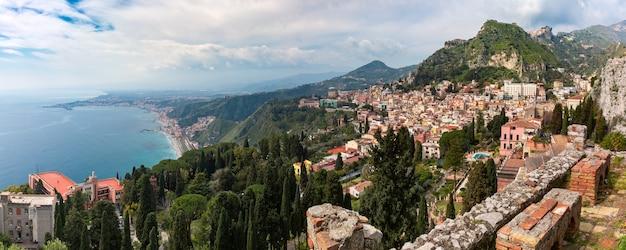 Vista panoramica del centro storico di taormina, della baia di giardini-naxos e del mar mediterraneo in una giornata di sole dall'antico teatro greco, sicilia, italia