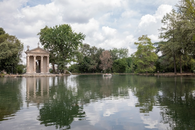 Vista panoramica del tempio di asclepio (tempio di esculapio) e del lago nel parco pubblico di villa borghese. giornata estiva e cielo azzurro