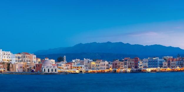 Vista panoramica della banchina veneziana di chania con la moschea di kucuk hasan pasha durante l'ora blu crepuscolare, creta, grecia