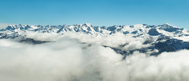 La vista panoramica delle montagne innevate di inverno varia in nuvole in abkhazia al fondo del cielo blu