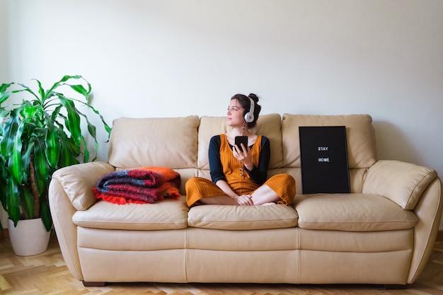 Vista panoramica della donna che ascolta la musica a casa. stare a casa. malattia da virus pandemico covida 19. concetto di salute.