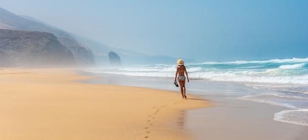 Panoramica di un giovane turista con un cappello che cammina da solo sulla spiaggia di cofete del parco naturale di jandia, barlovento, a sud di fuerteventura, isole canarie. spagna