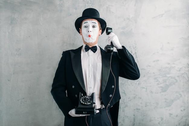 Attore di pantomima che si esibisce con il telefono retrò
