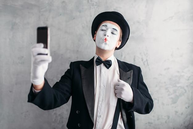 L'attore della pantomima con la maschera per il trucco fa selfie sulla fotocamera. commedia in abito, guanti e cappello